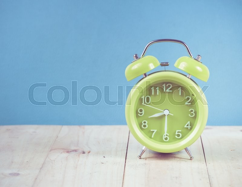 Stock image of 'Green alarm clock on wood,vintage color toned image'