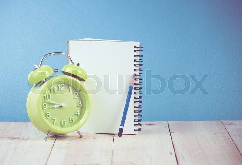 Stock image of 'Green alarm clock and Notebook Paper with Text Space on wood,blue background'