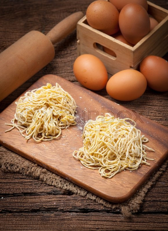 Stock image of 'Yellow noodles drying with eggs on wood background'