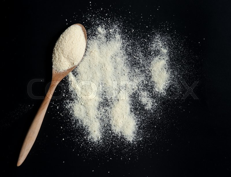 Stock image of 'Close up of powdered milk and spoon for baby on a black slate'