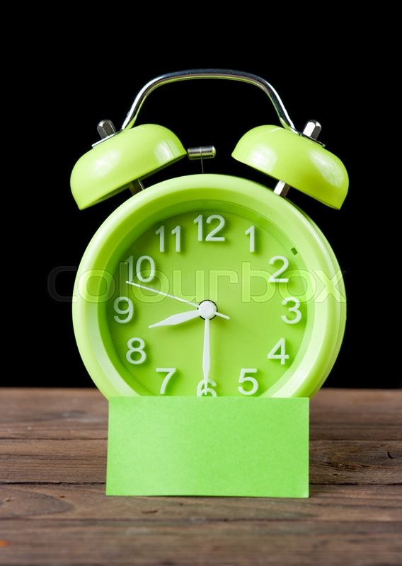 Stock image of 'Green alarm clock and sticky paper with Text Space isolated on white background,dark background'