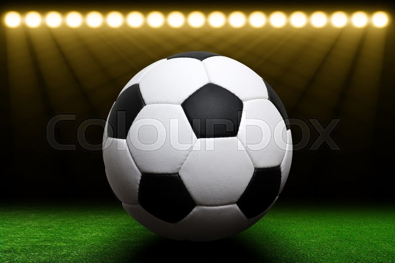 Stock image of 'Soccer ball on green stadium, arena in night illuminated bright spotlights'