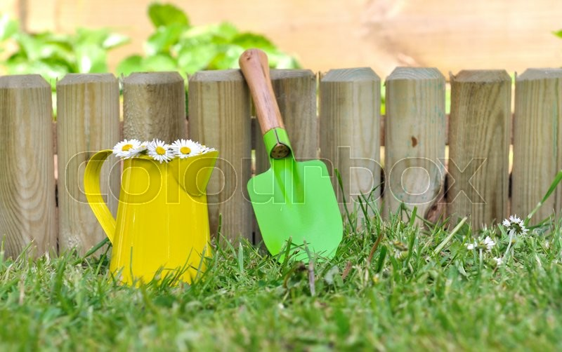 Stock image of 'colorful little shovel and can againt a wooden border in garden '
