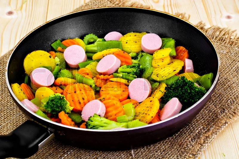 Stock image of 'Steamed Vegetables Potatoes, Carrots and Broccoli with Sausages in a Pan Studio Photo'