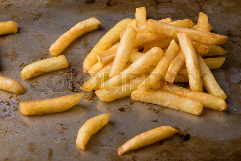 Stock image of 'fresh yellow fries on grungy steel plate'