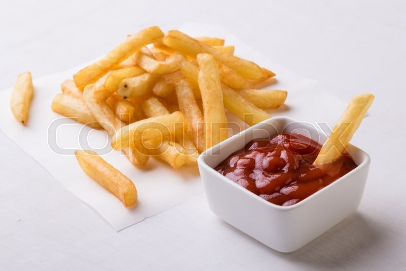 Stock image of 'fresh yellow fries on a white table with ketchup'