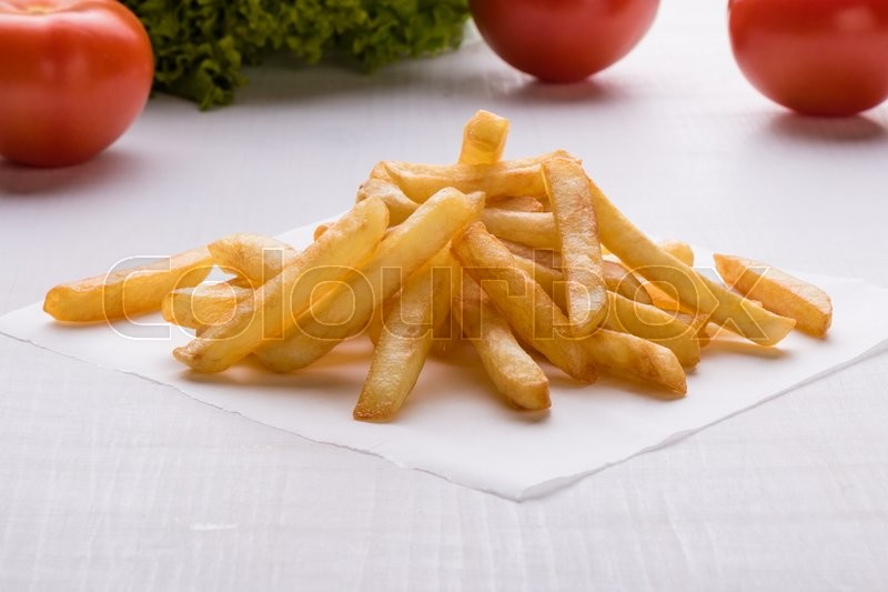 Stock image of 'fresh yellow fries on white table with vegetables'