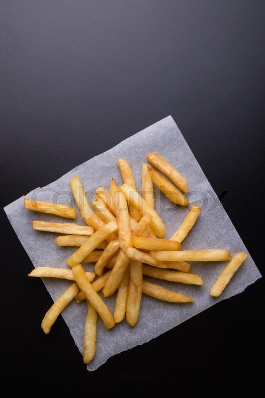 Stock image of 'fresh yellow fries on a black table'
