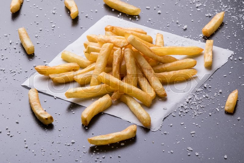 Stock image of 'fresh yellow fries on a black table with sea salt'
