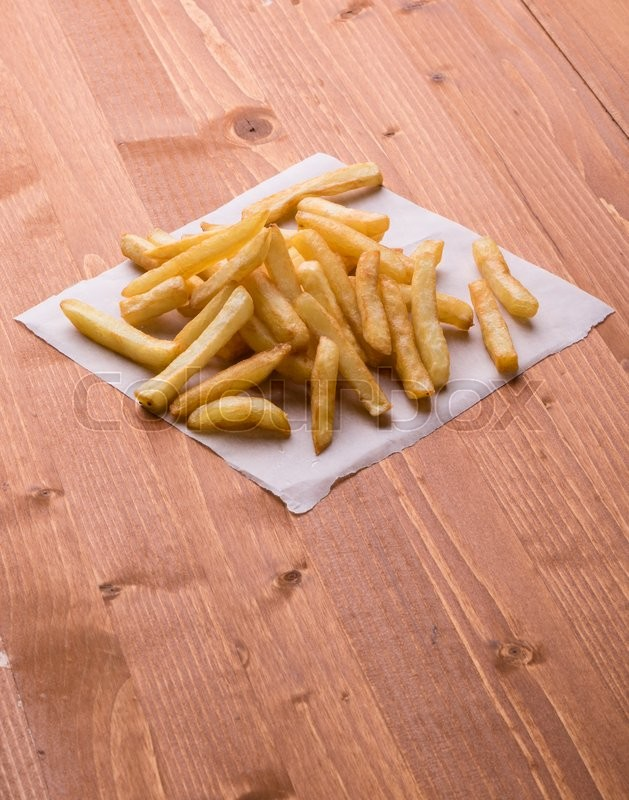 Stock image of 'fresh yellow fries on a wooden table'