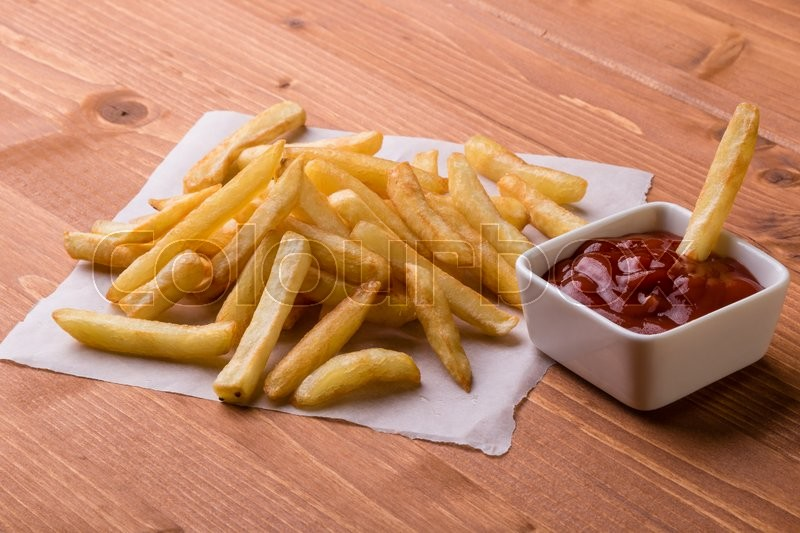 Stock image of 'fresh yellow fries on a wooden table with ketchup'