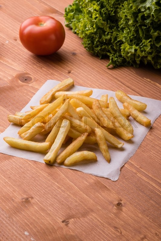 Stock image of 'fresh yellow fries on a wooden table with vegetables'