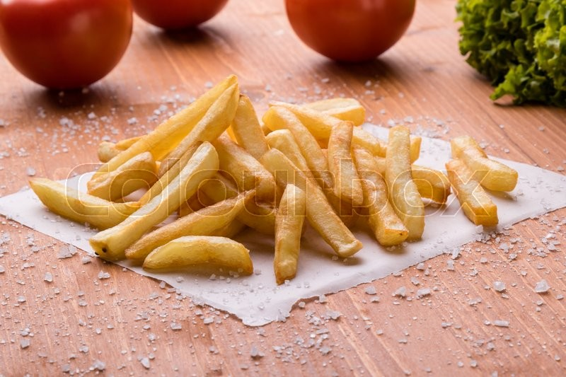 Stock image of 'fresh yellow fries on a wooden table with sea salt'