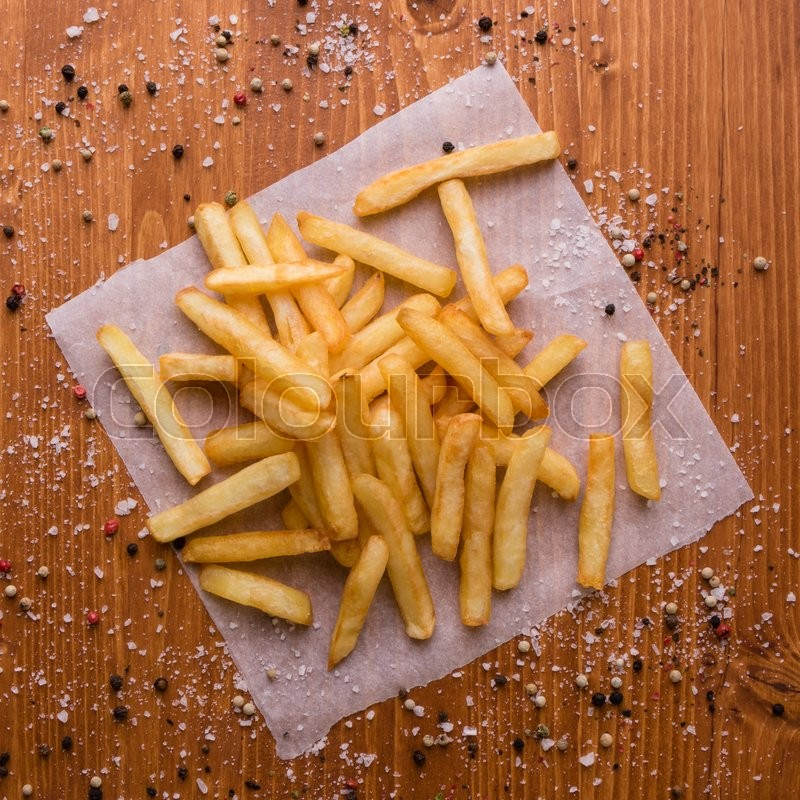 Stock image of 'fresh yellow fries on a wooden table with peppercorn seasoning'