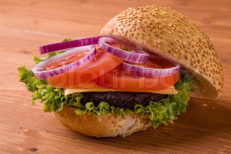 Stock image of 'tasty classic homemade hamburger on wooden table'