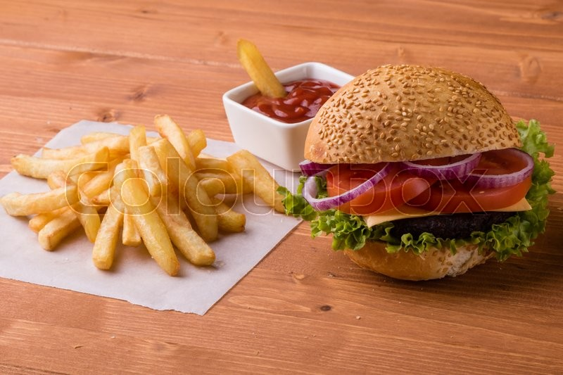 Stock image of 'tasty classic homemade hamburger on wooden table with fries'