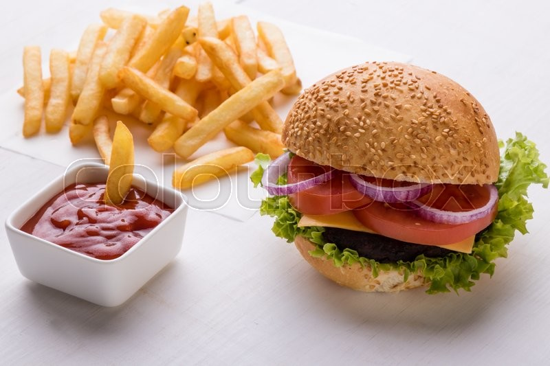 Stock image of 'tasty classic homemade hamburger on white table with fries'