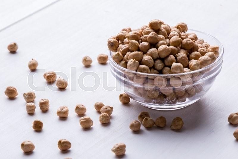 Stock image of 'dry chickpeas on white table in a bowl'