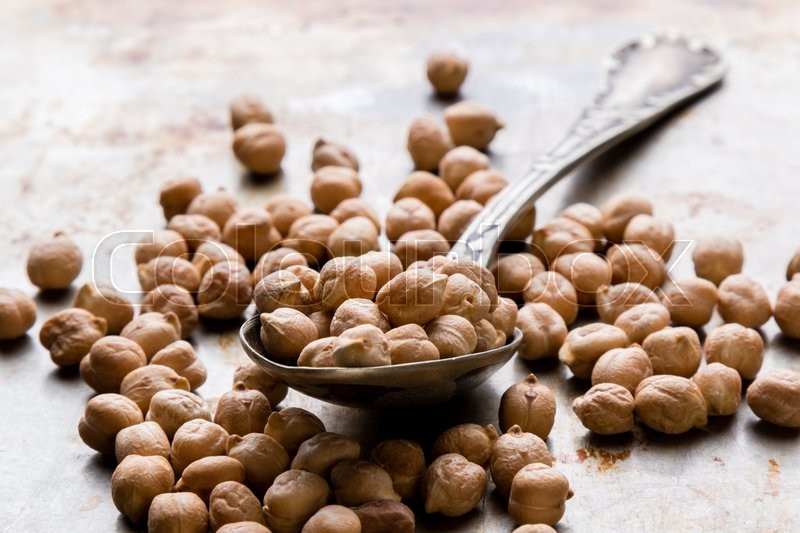 Stock image of 'dry brown chickpeas on steel plate with spoon'
