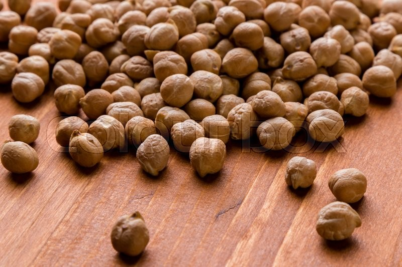 Stock image of 'dry brown healthy chickpeas on wooden table'