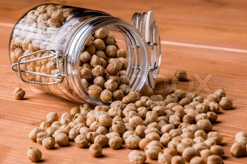 Stock image of 'dry brown chickpeas in glass jar on wooden table'