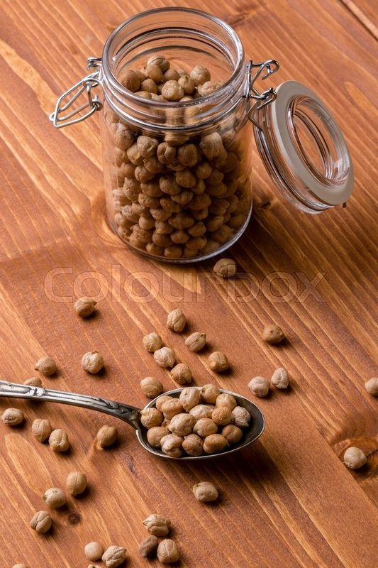 Stock image of 'dry brown chickpeas on wooden table with spoon'