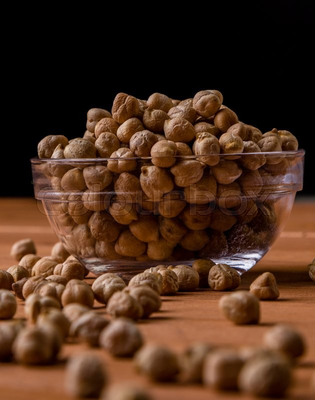 Stock image of 'dry brown chickpeas in a glass bowl on wooden table'
