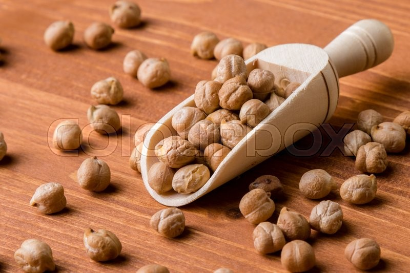 Stock image of 'dry brown chickpeas with wooden scoop on table'