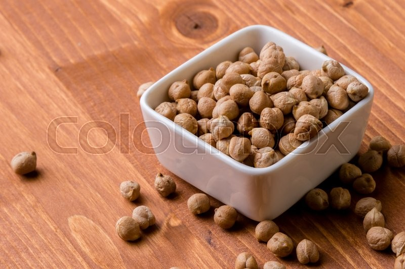 Stock image of 'dry brown chickpeas in a bowl on wooden table'