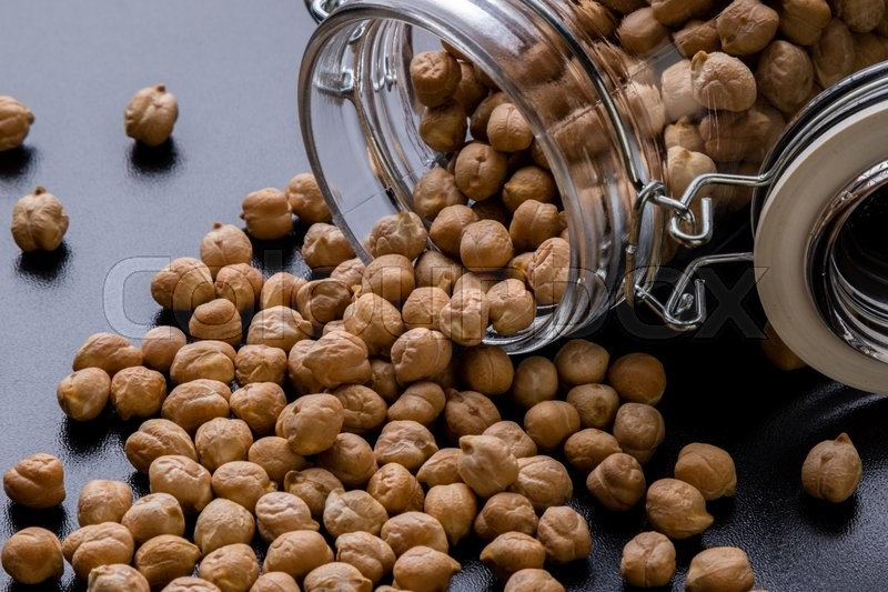 Stock image of 'dry brown chickpeas in glass jar on black table'
