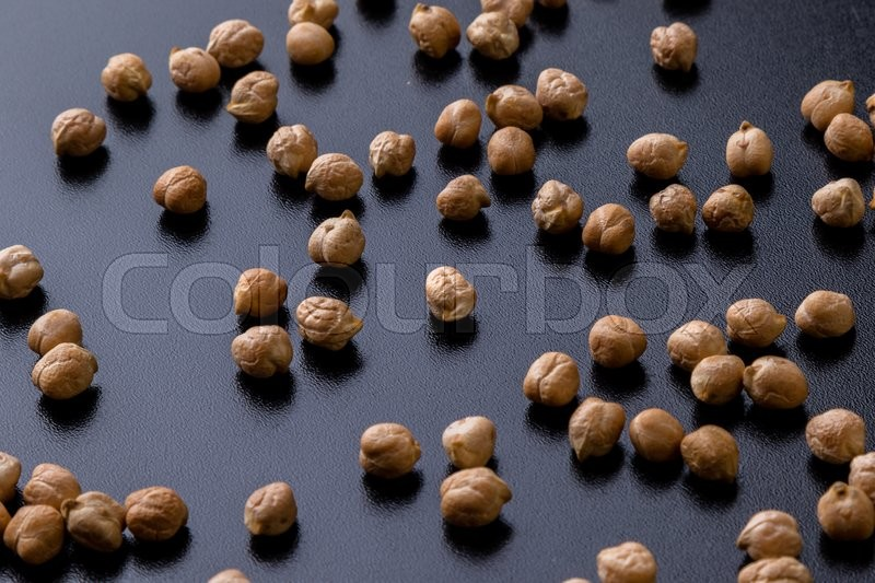 Stock image of 'dry brown chickpeas scattered on a black table'
