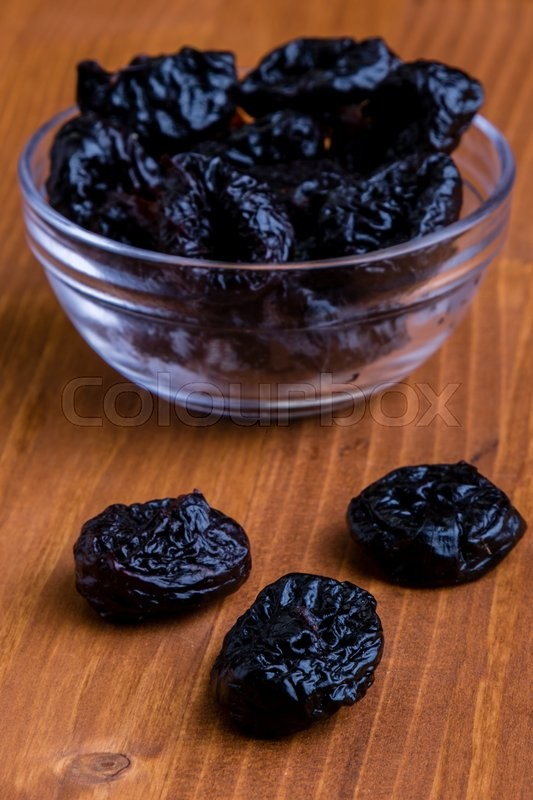 Stock image of 'organic sweet dark prunes on wooden table'