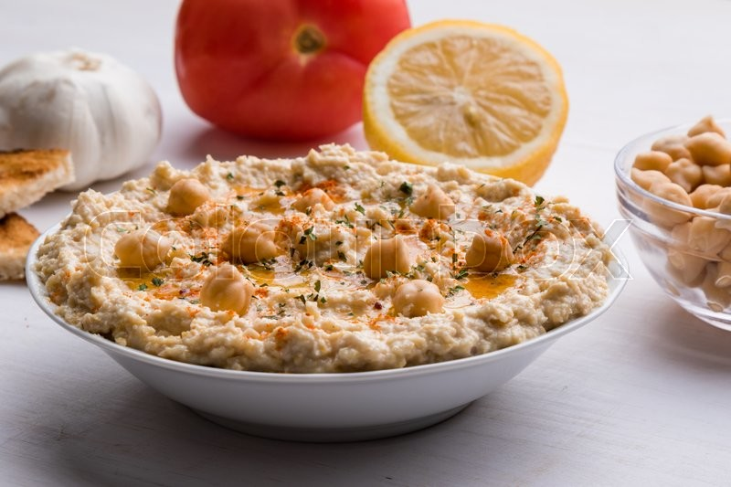 Stock image of 'home made hummus in bowl on white table'