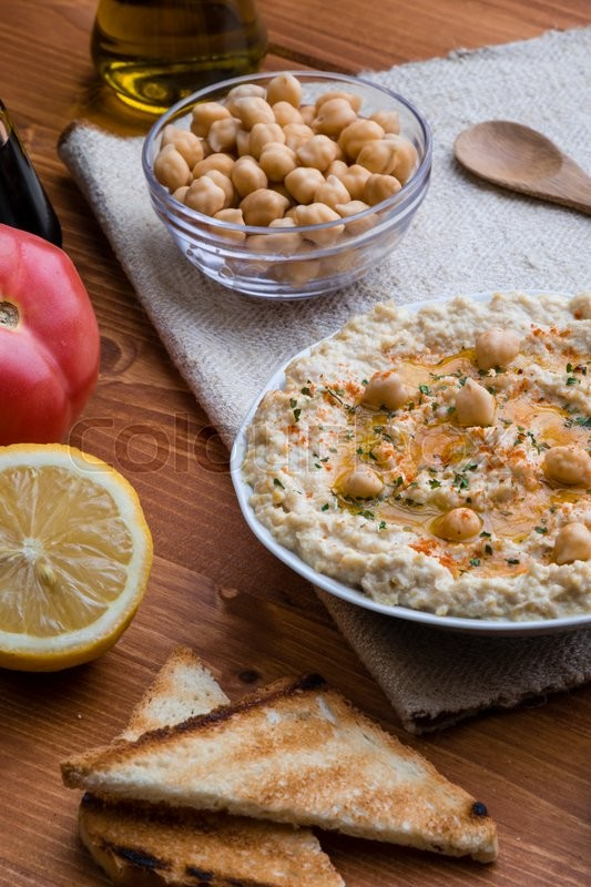 Stock image of 'creamy delicious fresh home made hummus on wooden table'