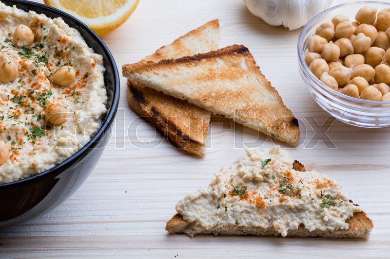 Stock image of 'creamy delicious fresh home made hummus with toast'