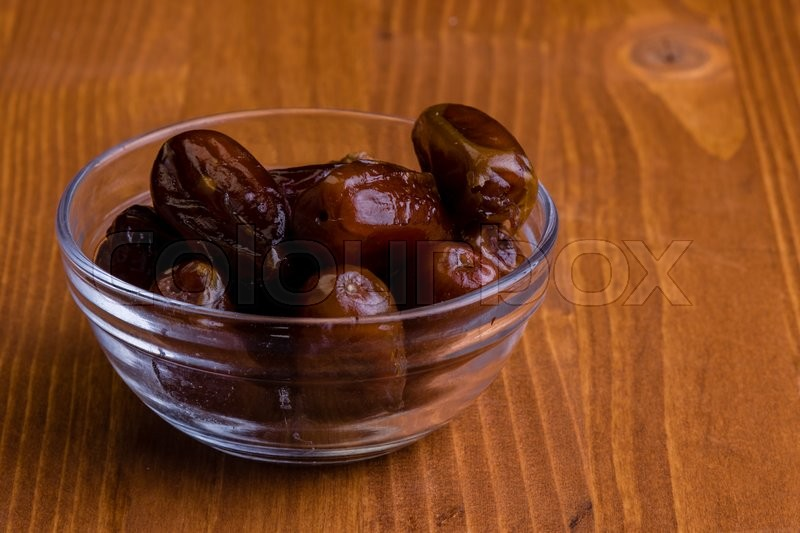 Stock image of 'sweet dried dates fruit on wooden table'