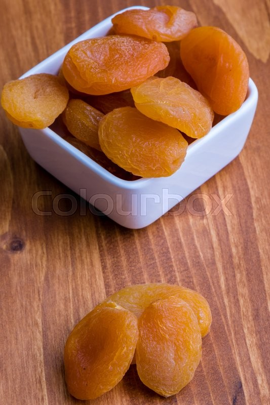 Stock image of 'sweet dried orange peach on wooden table'