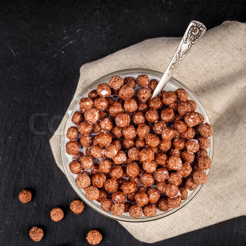 Stock image of 'Healthy breakfast. Chocolate cereal balls in bowl with milk on slate background.'