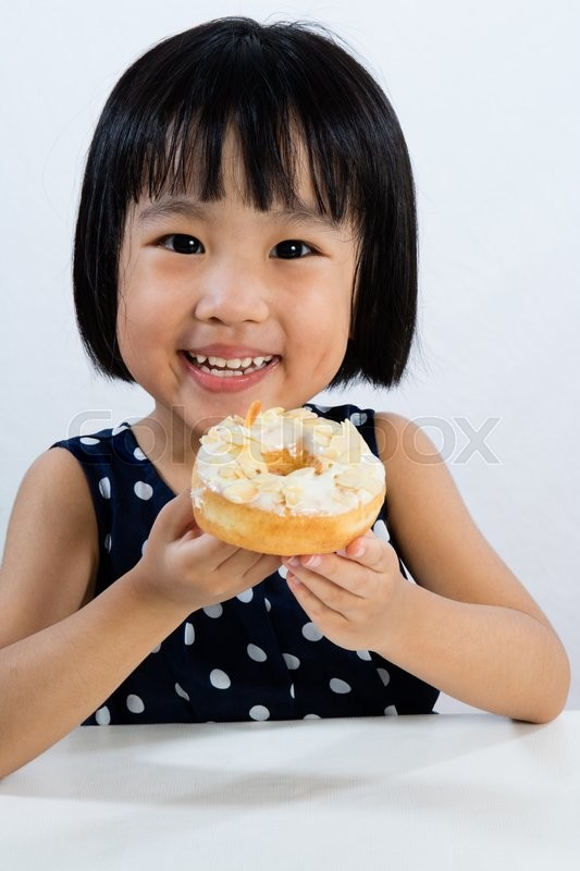 Stock image of 'Asian Little Chinese Girl Eating Donuts in isolated White Background'