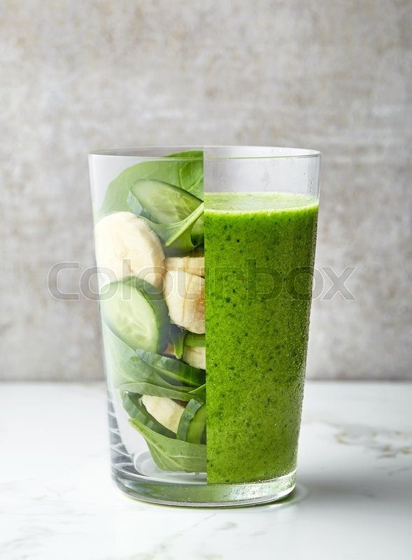 Stock image of 'glass of green smoothie on gray kitchen table'