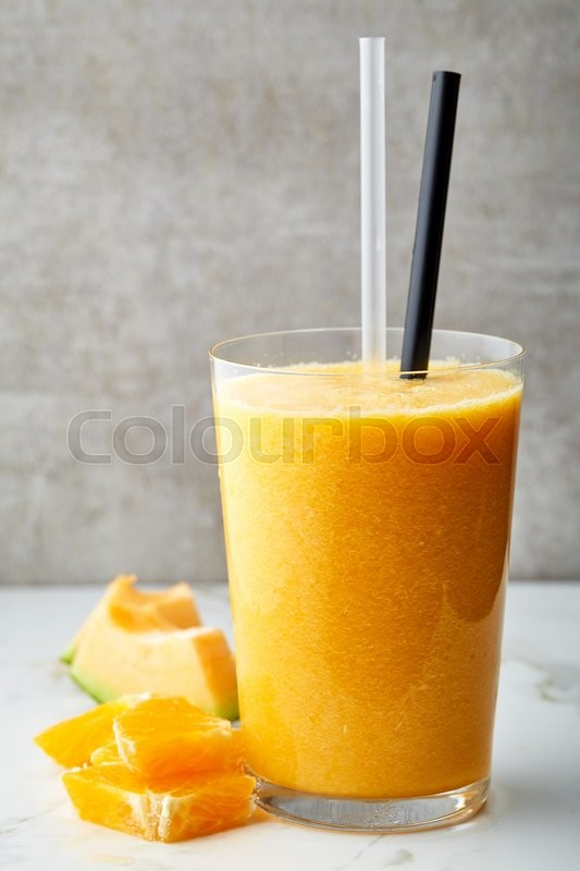 Stock image of 'glass of yellow orange and melon smoothie on gray kitchen table'