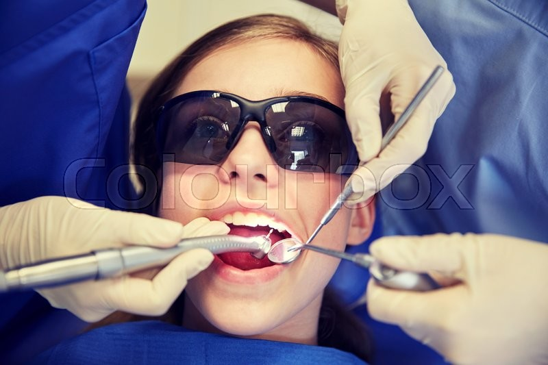 Stock image of 'people, medicine, stomatology and health care concept - female dentists with mirror, drill and probe treating patient girl teeth at dental clinic office'