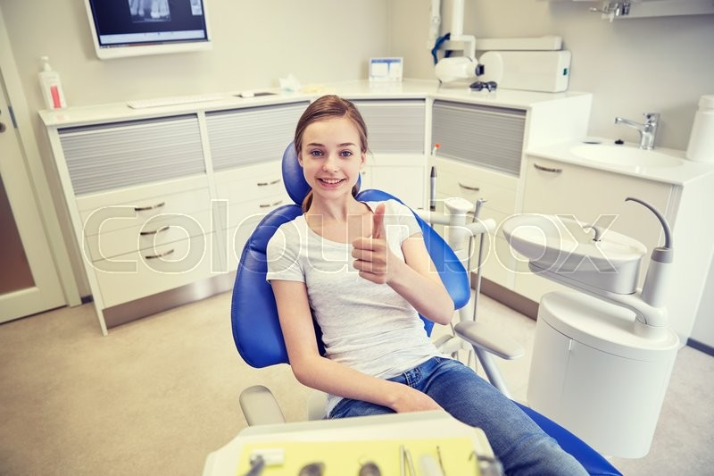 Stock image of 'people, medicine, stomatology and health care concept - happy patient girl showing thumbs up at dental clinic office'