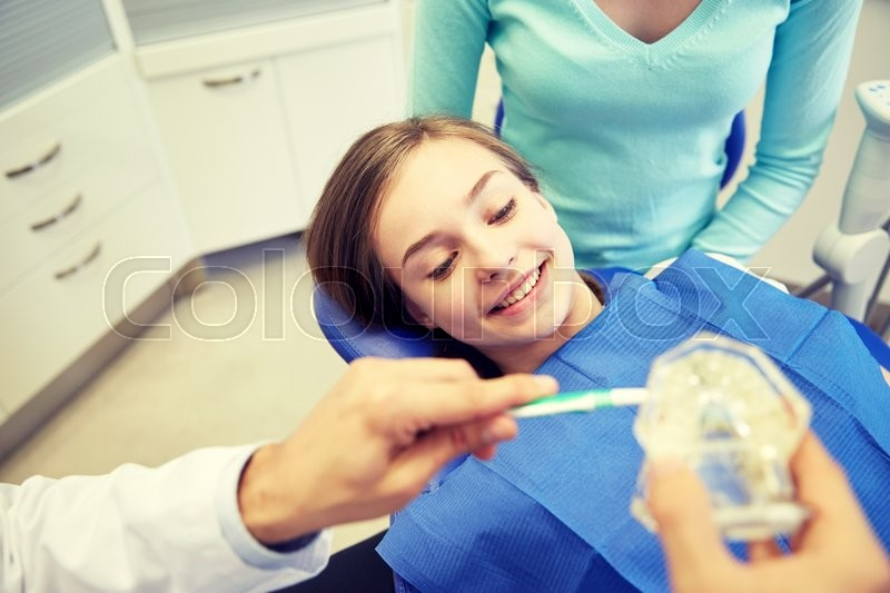 Stock image of 'people, medicine, stomatology and health care concept - happy male dentist with toothbrush and jaw layout showing how to brush teeth to patient girl and her mother at dental clinic office'