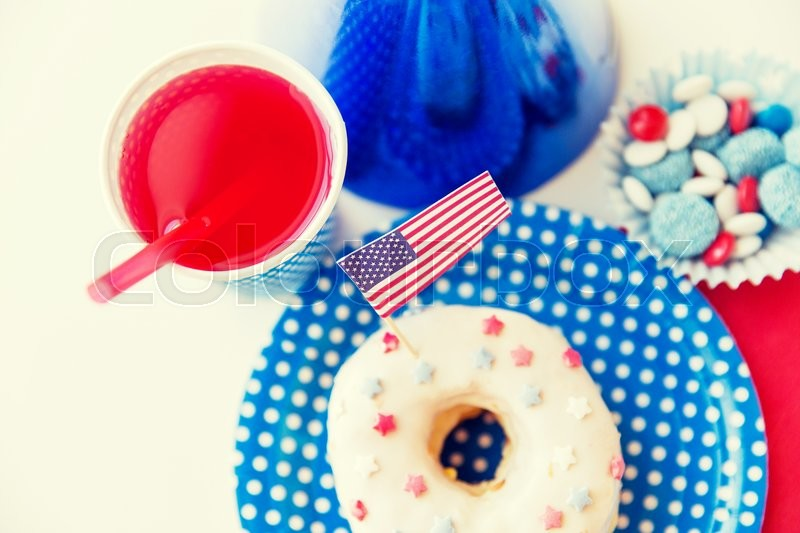 Stock image of 'american independence day, celebration, patriotism and holidays concept - close up of glazed sweet donut with juice and candies in disposable tableware at 4th july party from top'