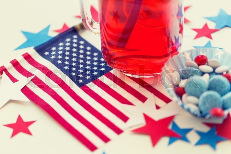 Stock image of 'american independence day, celebration, patriotism and holidays concept - close up of juice glass, flag and candies at 4th july party'