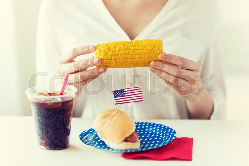 Stock image of 'american independence day, celebration, patriotism and holidays concept - close up of woman hands holding corn with hot dog and cola drink in plastic cup on 4th july party'