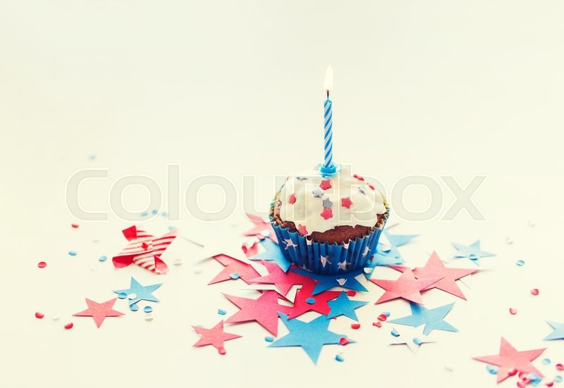 Stock image of 'independence day, celebration, patriotism and holidays concept - close up of glazed cupcake or muffin with burning candle and stars cofetti decoration on table at 4th july party'