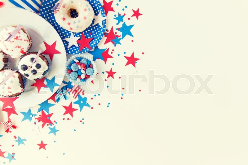 Stock image of 'independence day, celebration, patriotism and holidays concept - close up of glazed cupcakes or muffins decorated with american flags, donut and red blue candies on plate at 4th july party'