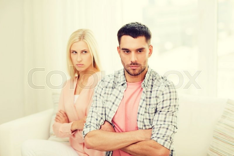 Stock image of 'people, relationship difficulties, conflict and family concept - unhappy couple having argument at home'
